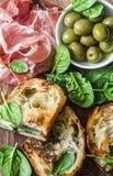 关闭熏火腿,橄榄,在木背景,顶视图的烤无盐干酪菠菜三明治 地中海样式快餐, appe 免版税库存照片