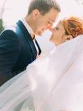 关闭爱恋看彼此的美丽的redhair新娘和英俊的新郎画象  免版税库存图片