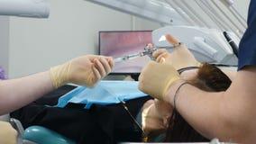 关闭牙医办公室和女性患者牙齿椅子的 有牙齿麻醉剂的男性辅助举行的注射器 股票视频