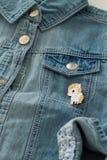 关闭牛仔布有凉快的图表别针的牛仔裤夹克看法  免版税库存照片