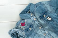 关闭牛仔布有凉快的图表别针的牛仔裤夹克看法  免版税库存图片