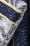 关闭牛仔裤片段织边 棉花牛仔布详细资料织品牛仔裤纹理 免版税库存图片
