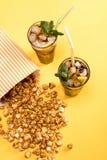 关闭玉米花和被冰的茶看法在玻璃在黄色 免版税库存图片