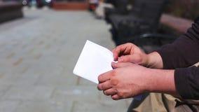 关闭现金信封在手上 在纸信封的金钱奖金 拿着与金钱的一个人一个信封 ?? 股票视频