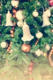 关闭球和响铃在圣诞树与减速火箭的过滤器作用(葡萄酒样式) 库存照片