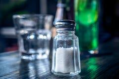 关闭瓶在一张木桌上的盐瓶的图象在咖啡馆,巴厘岛 免版税图库摄影