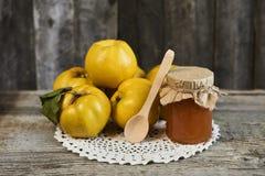关闭瓶子果酱和柑橘与叶子在木土气 图库摄影