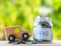 关闭瓶子硬币并且戏弄在木桌上的汽车在迷离背景,存金钱为汽车和企业概念 免版税库存图片