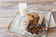 关闭甜食物和乳白玻璃在桌上 免版税库存图片