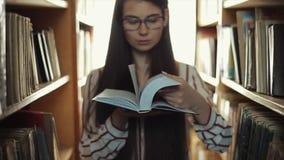 关闭生叶通过书的玻璃的美丽的少女 股票录像