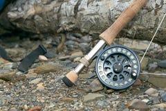 关闭用假蝇钓鱼标尺和卷轴在河岸 免版税图库摄影