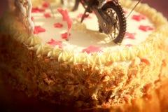 关闭用摩托车和红色星装饰的生日蛋糕 库存图片