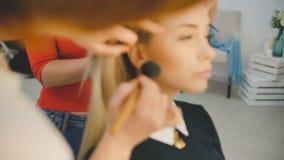 关闭申请在美好的年轻肉欲的模型的面孔的专业化妆师射击构成与 影视素材