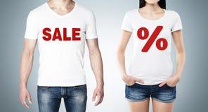 关闭男人和妇女的身体的白色T恤杉有红色百分率符号和词的'销售'在胸口 免版税库存图片