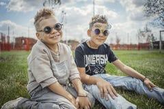 关闭男孩在公园坐绿草 愉快概念的系列 库存图片
