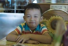 关闭男孩就座的射击在一把木椅子的 免版税库存照片