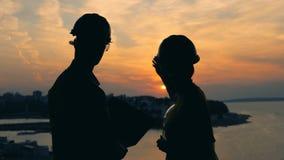 关闭男性和一女工`剪影反对日落风景 股票录像