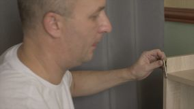 关闭男性手紧的螺丝由在家运转电的螺丝刀 住所改善DIY概念 检查凹道的人 影视素材