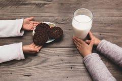 关闭留下曲奇饼和牛奶的两个孩子在圣诞老人的桌 免版税库存照片