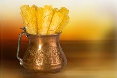 关闭番红花冰糖在一个传统铜碗的糖水晶在它是常用的是Diss的白色背景 免版税库存图片