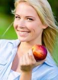 关闭白肤金发的妇女用红色苹果 图库摄影