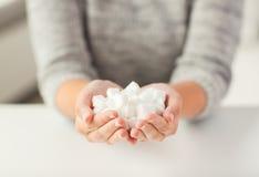 关闭白色块糖在妇女手上 免版税库存图片