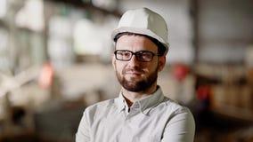 关闭白色衬衣、防护站立在建筑区域的盔甲和镜片的有胡子的人 年轻建筑师 股票录像