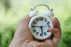 关闭白色闹钟在妇女手上作为事务或时间 库存照片