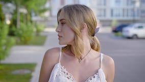 关闭白色鞋带礼服的微笑在漫步,她的在的卷发浮游物的年轻美丽的白肤金发的妇女画象  股票视频