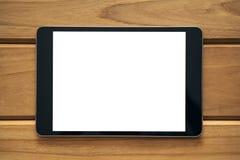 关闭的大模型图象黑片剂个人计算机的有在葡萄酒木桌上的空白的白色屏幕的 免版税库存照片