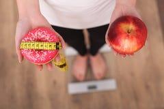关闭的妇女做出在苹果和多福饼之间的观点选择与被弄脏的标度在背景 在背景空白弓概念节食的显示评定编号附近自己的缩放比例磁带文本附加的空白视窗包裹了您 库存照片