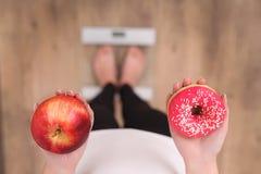 关闭的妇女做出在苹果和多福饼之间的观点选择与被弄脏的标度在背景 在背景空白弓概念节食的显示评定编号附近自己的缩放比例磁带文本附加的空白视窗包裹了您 免版税库存图片