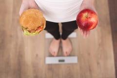 关闭的妇女做出在苹果和汉堡包之间的观点选择 免版税库存照片
