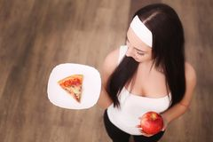 关闭的妇女做出在苹果和薄饼机智之间的观点选择 免版税库存照片