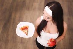 关闭的妇女做出在苹果和薄饼机智之间的观点选择 免版税库存图片