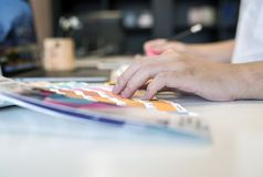 关闭的男性设计师指向在颜色树荫样片的观点 免版税库存照片