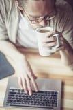 关闭的自由职业者人键入在膝上型计算机的观点,喝茶 库存照片
