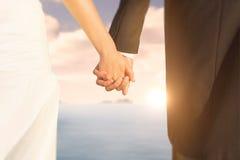 关闭的综合图象握他们的手的逗人喜爱的年轻新婚佳偶 免版税图库摄影