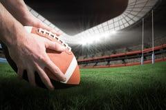 关闭的综合图象3D观点的美国橄榄球运动员为反弹球射门做准备 免版税库存图片