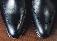 关闭皮革人` s鞋子的图片在木背景的 免版税图库摄影