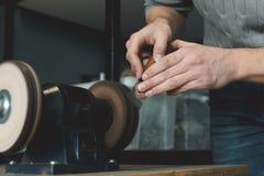 关闭皮革工匠削尖切开的皮革刀子在沙磨机 r 创造的小企业的概念 图库摄影