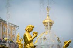 关闭盛大小瀑布喷泉金黄雕象在Peterhof宫殿在圣彼德堡,俄罗斯 库存图片