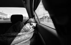 关闭相当有太阳镜的年轻亚裔妇女用毯子掩盖自己和睡觉在后座 库存照片