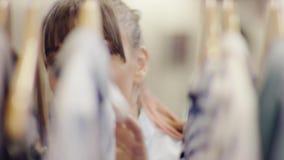 关闭看从在一个机架的衣裳的后面突然上升了妇女在服装店 股票录像