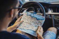 关闭看在轮子后的年轻人地图在汽车 免版税库存图片