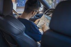 关闭看在轮子后的年轻人地图在汽车 免版税库存照片