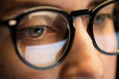 关闭看屏幕的玻璃的妇女 免版税库存图片