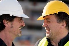 关闭看彼此的两名微笑的建筑工人 免版税库存图片