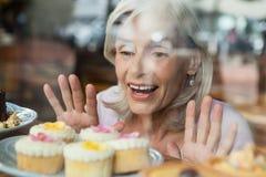 关闭看杯形蛋糕的愉快的妇女被看见通过玻璃窗 库存照片
