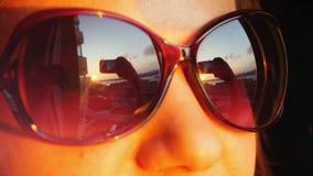 关闭看法少妇在太阳镜的` s面孔,站立在窗口,并且拿着智能手机拍在日落的照片  免版税库存照片